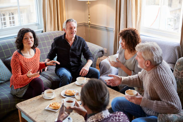 Group Of Middle Aged Friends Meeting Around Table In Coffee Shop stock photo