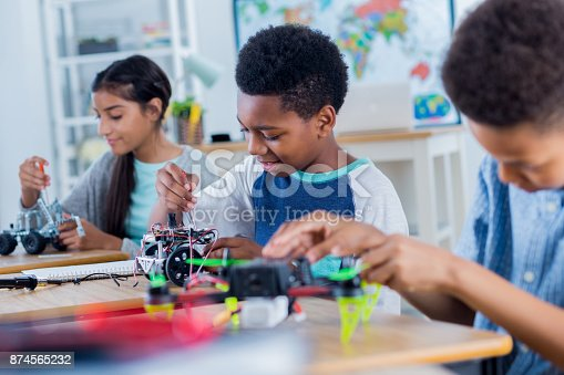 Happy middle school students work on projects during after school robotics club. They are building robotic vehicles and drones.