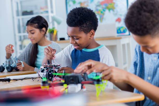 Group of middle school students work on robotics project stock photo