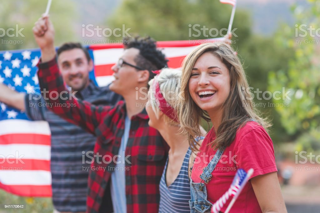 Group of millennial friends hold a large American flag stock photo