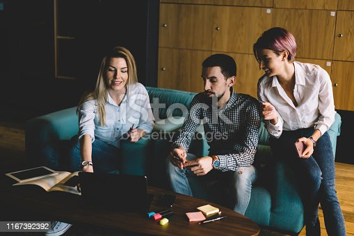 905130626 istock photo Group of millennial male and female colleagues having brainstorming session using netbook for networking, skilled coach making workshop for students of business school showing video on laptop computer 1167392392