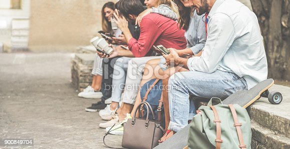 istock Group of millennials friends using smartphones  outdoor - Happy people having fun with technology trends after university lesson - Youth and friendship concept - Focus on right man mobile phone 900849704