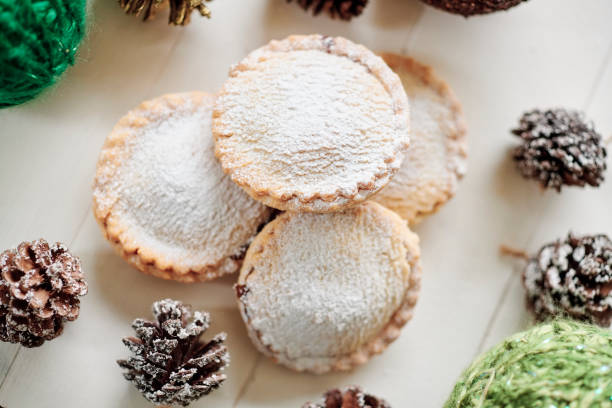 group of mince pies on a white table with pine cones and christmas decorations. stock photo