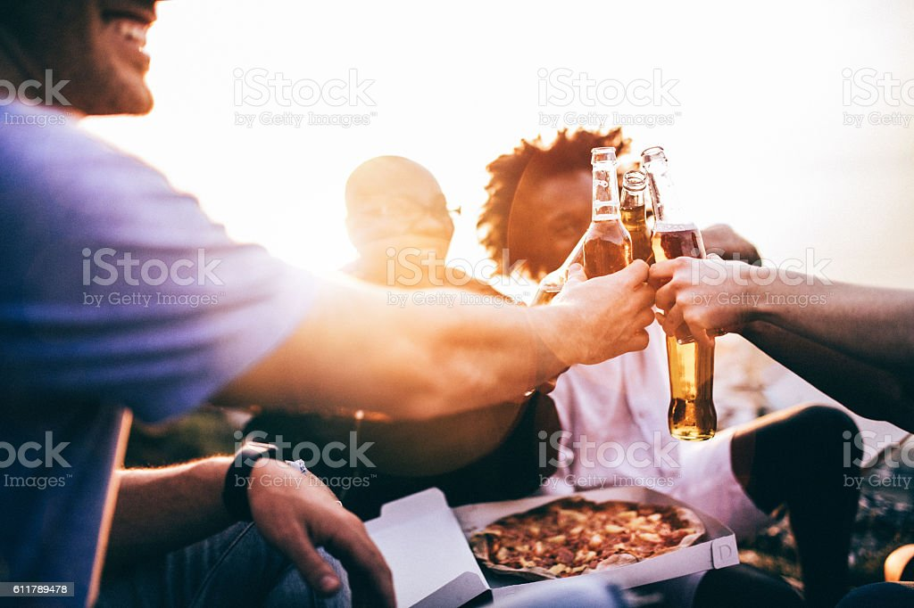 Group of mixed race friends enjoying beer and pizza at stock photo