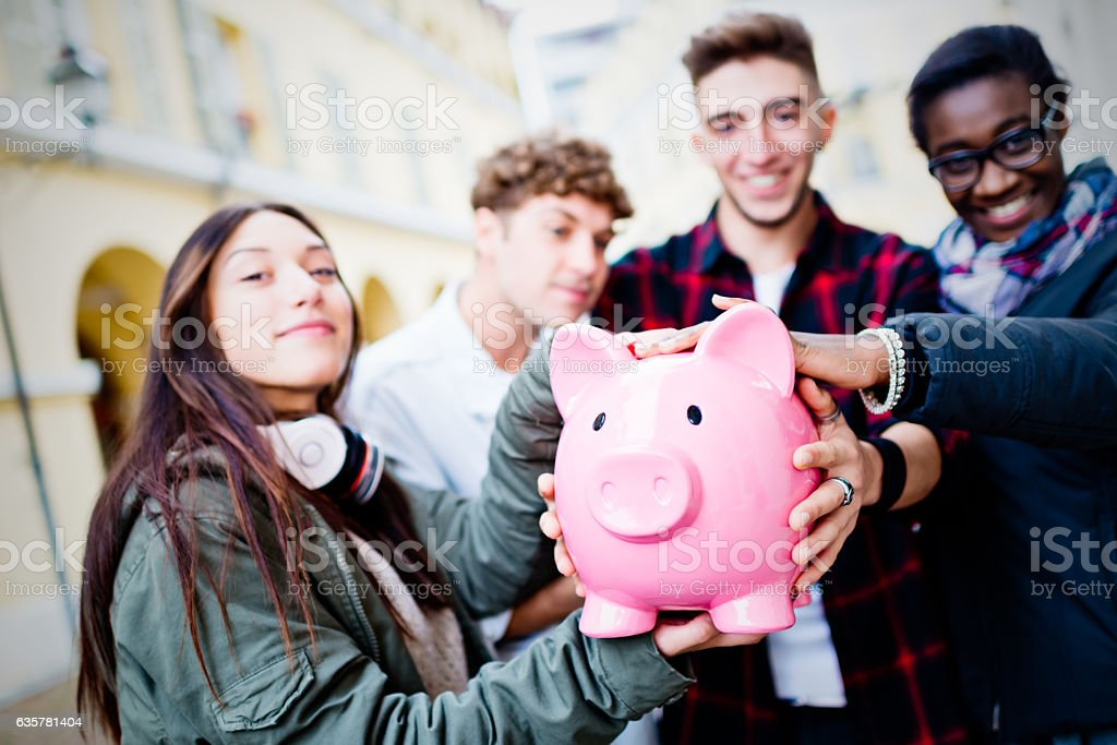 Group of mixed race people holding Piggy Bank stock photo