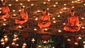 Chiang Mai, Thailand - November 28, 2012: Group of monks sitting meditation in the sacred ritual at Wat Phan Tao temple during the Loi Krathong Festival.