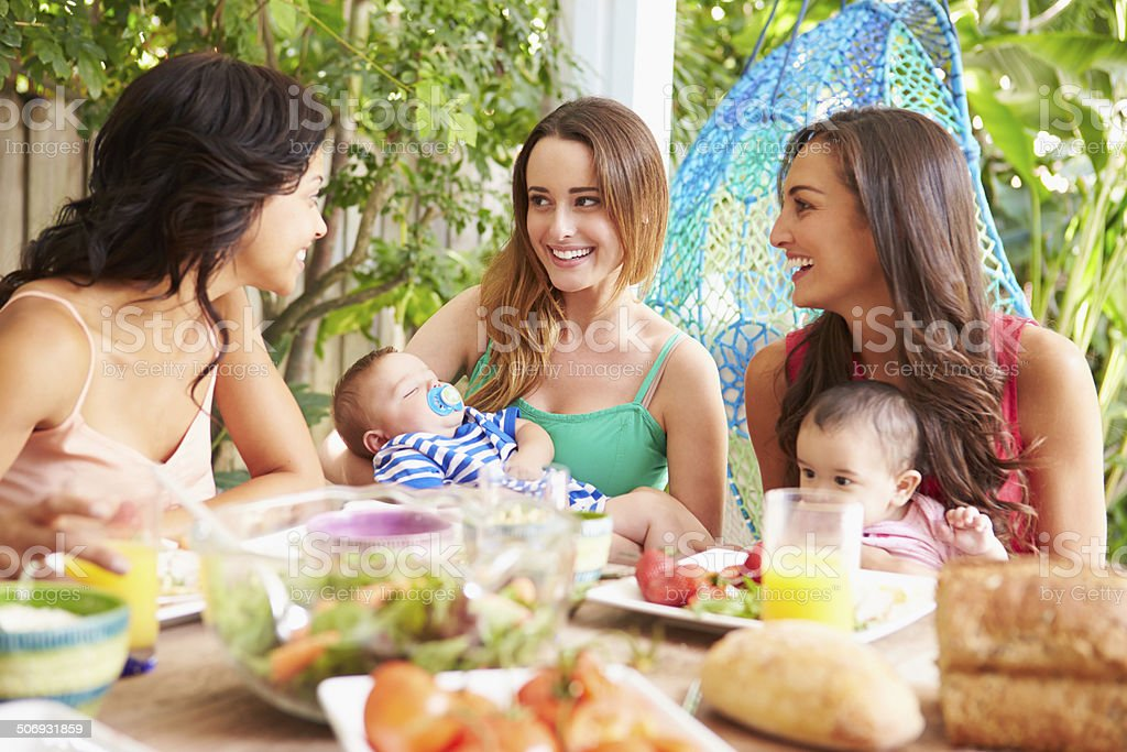 Group Of Mothers With Babies Enjoying Outdoor Meal At Home stock photo