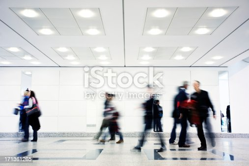 motion blur of commuters rushing in modern interior,