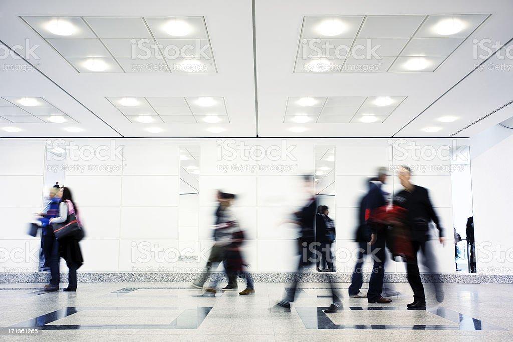 Group of Motion Blurred People Walking Through Illuminated Corridor stock photo