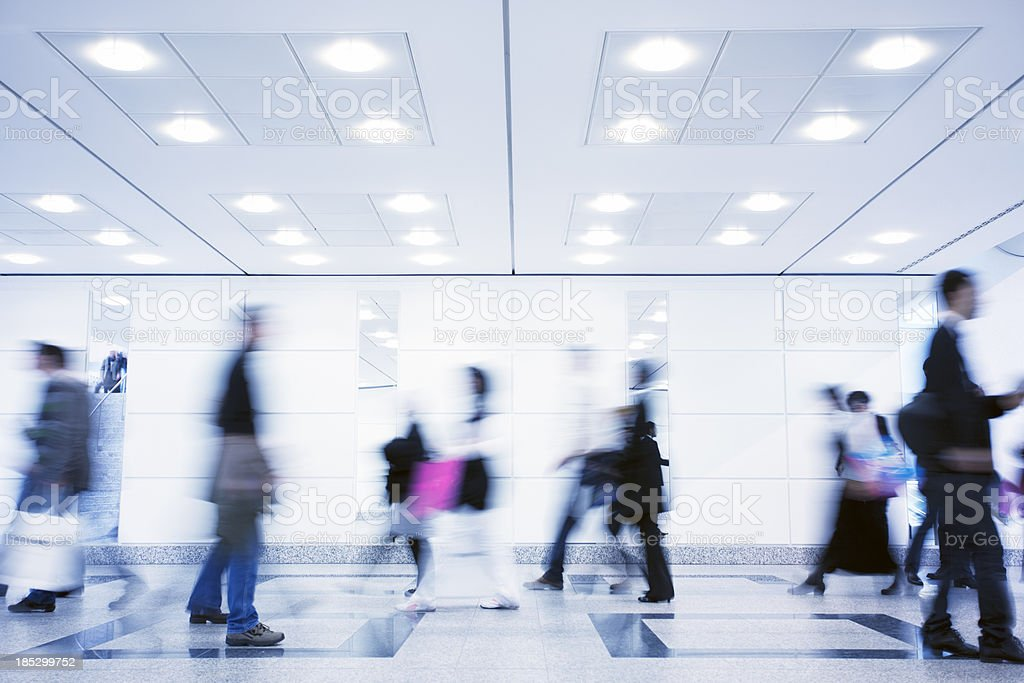 Group of Motion Blurred People Walking Through Illuminated Corridor royalty-free stock photo
