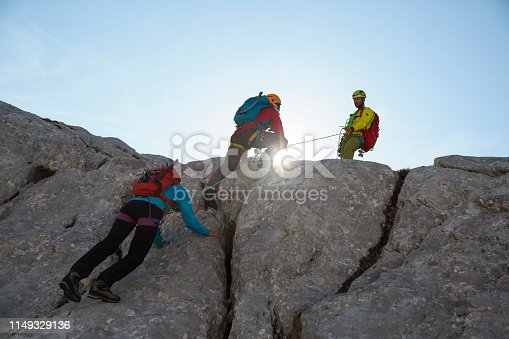Two men and a woman climbing mountain with all the equipment. Ropes, shoes, helmets, backpacks... One man is helping other two with rope.