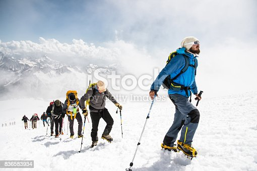 A group of mountaineers rises to the top of a snow-capped caucasian mountain against the backdrop of the rocky peaks of the mountains covered with snow.