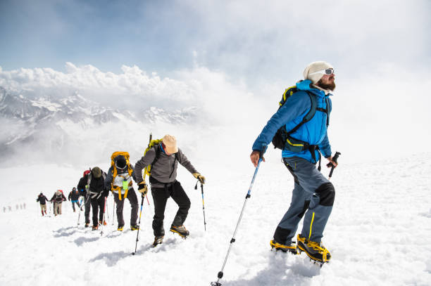 A group of mountaineers climbs to the top of a snow-capped mountain stock photo