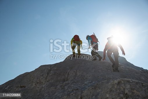 Three mountain climbers silhouettes against a blue sky with sun.
