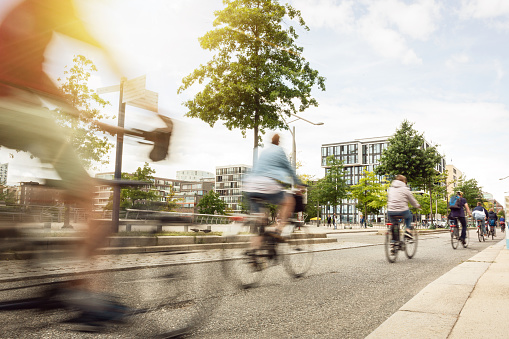 Motion blurred cyclists riding inside a city on a sunny day.