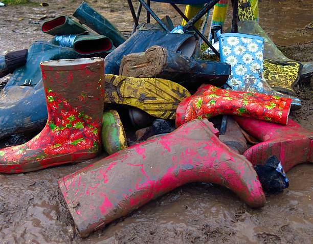 group of muddy wellies Wellington Boots discarded at music festival stock photo