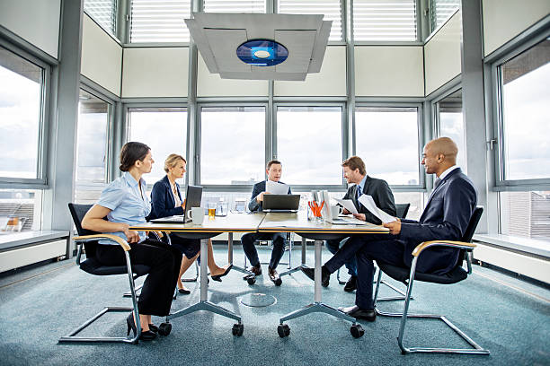 Group of multi ethnic executives in a meeting Group of multi ethnic executives discussing during a meeting in modern conference room governing board stock pictures, royalty-free photos & images