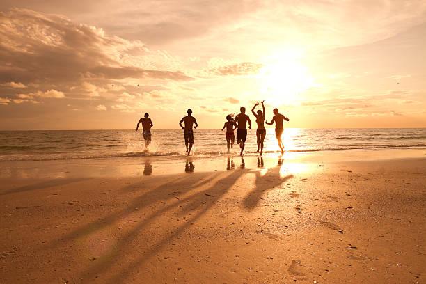 group of multi ethnic friends having fun at the beach - strandfeest stockfoto's en -beelden