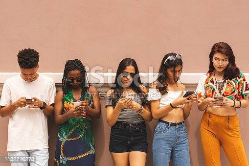 Group of multi ethnic latin teenagers using smartphone outdoors, standing in a row, leaning against a wall