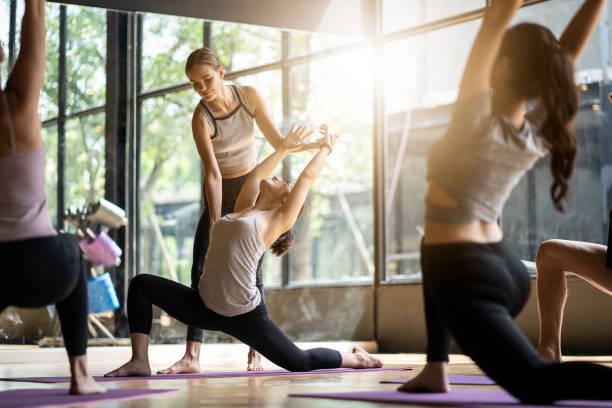 группа многоэтнических людей изучает класс йоги в фитнес-клубе. самка кавказского инструктора коучинг и настроить правильную позу для ази� - class стоковые фото и изображения