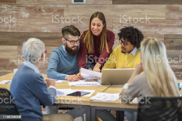 Group Of Multi Generation Business Colleagues In Open Hub Office Stock Photo - Download Image Now