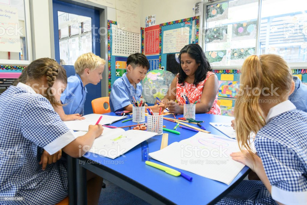 Group of multi racial school children in classroom with their teacher stock photo