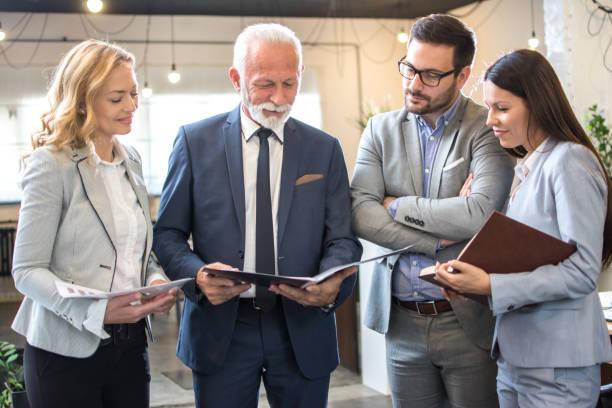 Gruppe von Geschäftsleuten im mehrjährigen Alter, die Papierdokumente gemeinsam im Büro analysieren – Foto