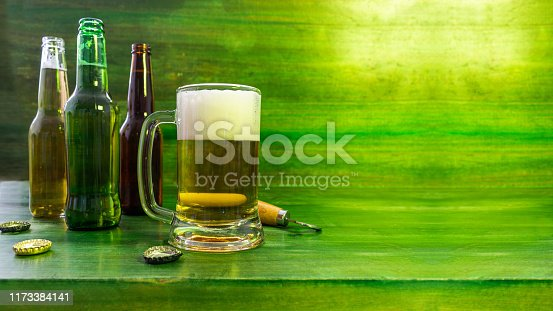 Still life with a beer mug with foam accompanied by several bottles and a bottle opener on a green textured wooden background