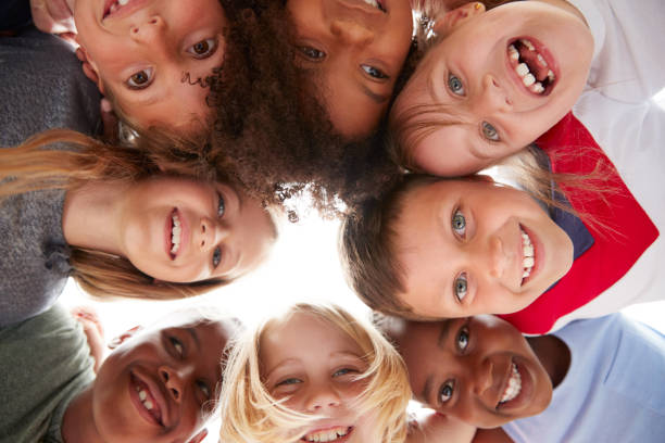 Group Of Multi-Cultural Children With Friends Looking Down Into Camera Group Of Multi-Cultural Children With Friends Looking Down Into Camera monkeybusinessimages stock pictures, royalty-free photos & images
