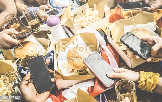 istock Group of multicultural friends having fun on smartphone at restaurant - Multiracial people hands using mobile smart phone at food sport bar - Technology addiction concept - Retro contrasted filter 955127402
