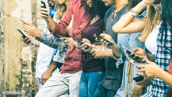 istock Group of multicultural friends using smartphone outdoors - People hands addicted by mobile smart phone - Technology concept with connected men and women - Shallow depth of field on vintage filter tone 872905048
