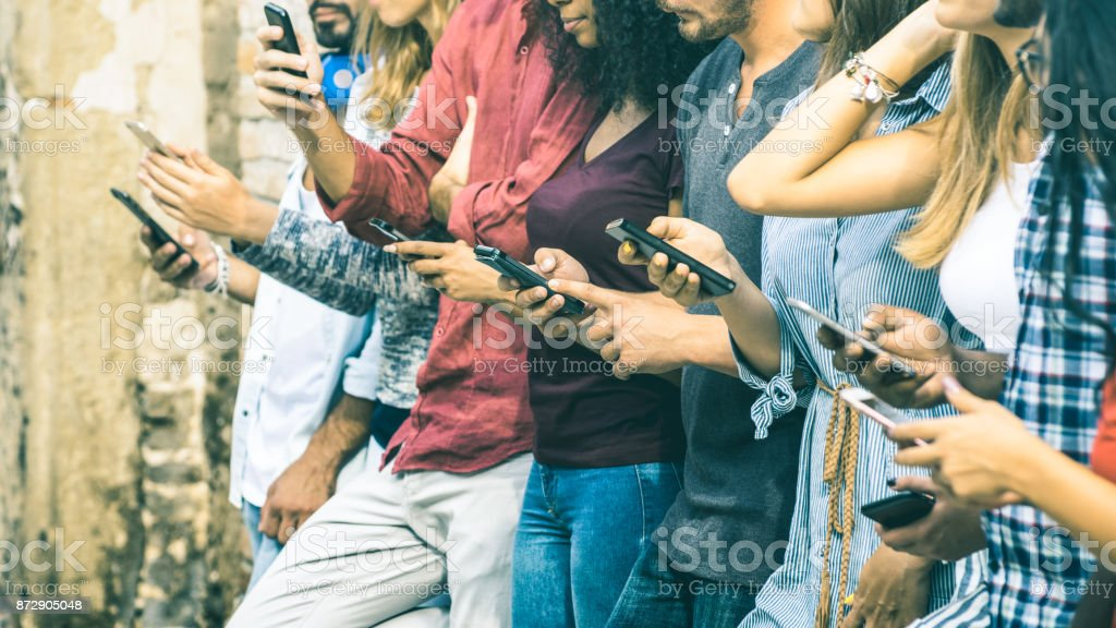 Group of multicultural friends using smartphone outdoors - People hands addicted by mobile smart phone - Technology concept with connected men and women - Shallow depth of field on vintage filter tone stock photo