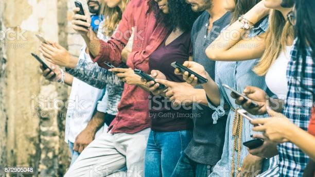 Gruppe Von Multikulturellen Freunde Mit Smartphone Outdoor Menschen Händen Durch Mobile Smartphone Technologiekonzept Mit Angeschlossenen Männer Und Frauen Geringe Schärfentiefe Auf Vintagefilter Ton Süchtig Stockfoto und mehr Bilder von Soziales Netzwerk