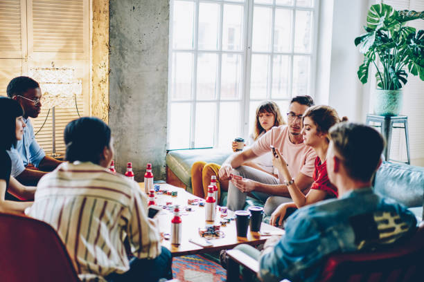 Group of multicultural young people dressed in casual wear playing in board game sitting at wooden table with alkohole and poker chips in flat.Hipster guys spending time together on gambling stock photo