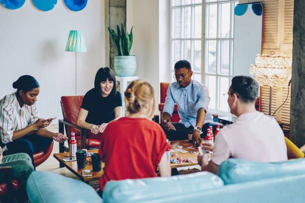 Group of multicultural young people in casual wear playing in poker game sitting at wooden table with alcohol beverage and chips.Diverse hipster guys spending time together on gambling stock photo