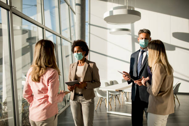 Group of multiethnic business people have a meeting and working in office while wear mask as protection from corona virus stock photo