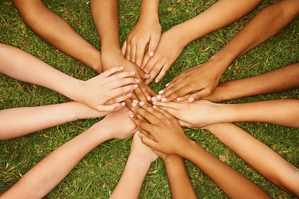 Group of multiethnic children with their hands together stock photo