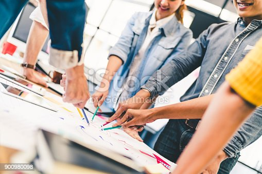 istock Group of multi-ethnic diverse team, business partner, or college students in project meeting at modern office or university. Five people pointing at diagram chart drawing. Creative or teamwork concept 900980098