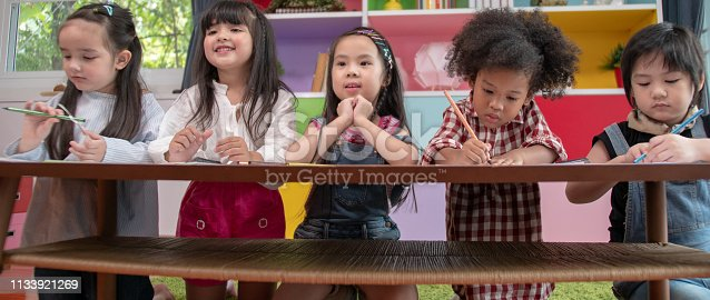 Group of multi-ethnic five little kids children African American, asian and Caucasian happiness together with friend to draw  colour pencil to full colour of picture with  in living room or class room