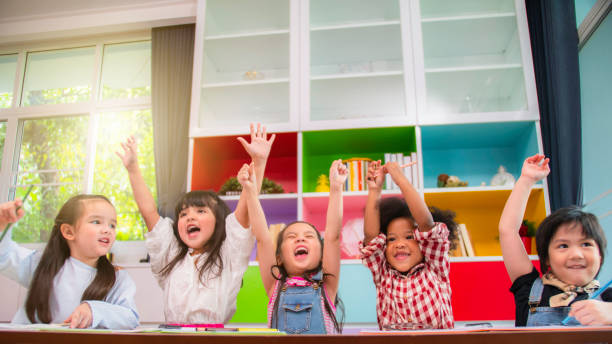 group of multi-ethnic five little kids children african american, asian and caucasian happiness together with friend to draw colour pencil to full colour of picture in living room or class room - preschool stock photos and pictures