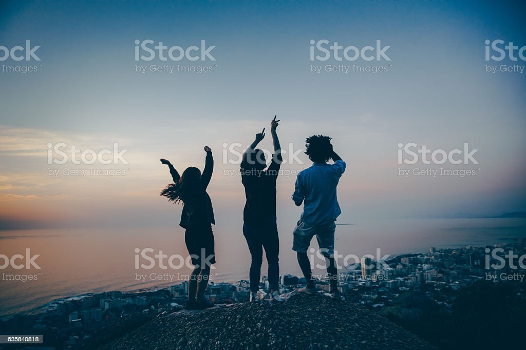 Group of multi-ethnic friends dancing outside on a rock at stock photo