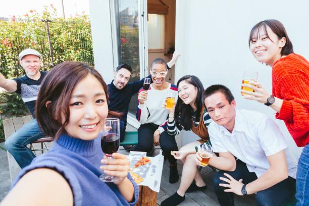 自宅パーティーを楽しんで多民族の友人のグループ - people of color ストックフォトと画像