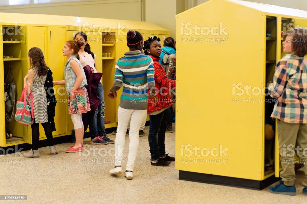 Group of multi-ethnic kids around lockers in elementary school. stock photo