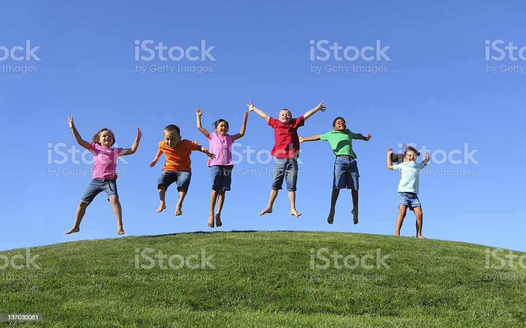 Group of multi-ethnic kids jumping together stock photo
