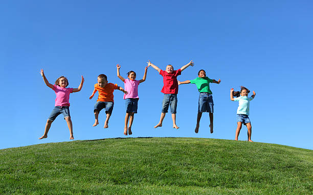 group of multi-ethnic kids jumping together - african youth jumping for joy stock photos and pictures