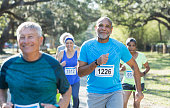 A group of five multi-ethnic seniors running in a race, wearing marathon bibs. The focus is on the African-American man in the middle foreground.
