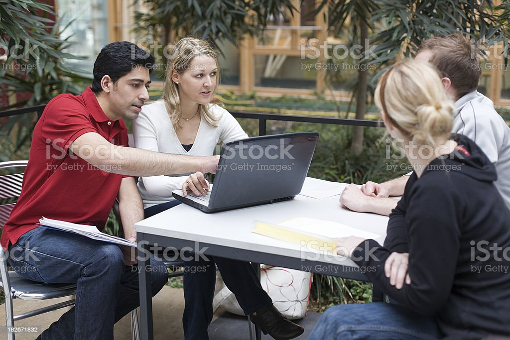 Group of multi-ethnic students in teamwork with laptop presentation (XXL) royalty-free stock photo