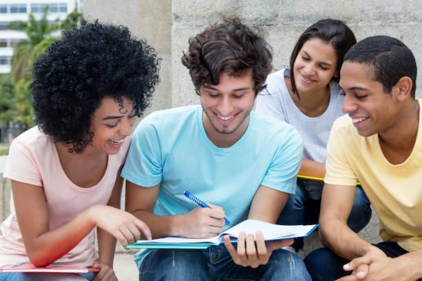 gruppe von multiethnischen studenten lernen im freien auf dem campus - studieren in deutschland stock-fotos und bilder
