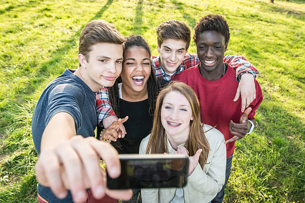 Group of multiethnic teenagers taking a selfie at park. stock photo