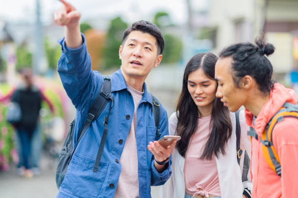 Group of multi-ethnic tourist friends checking smart phone for directions A group of multi-ethnic tourist friends are checking their smart phones for directions. southeast asian ethnicity stock pictures, royalty-free photos & images